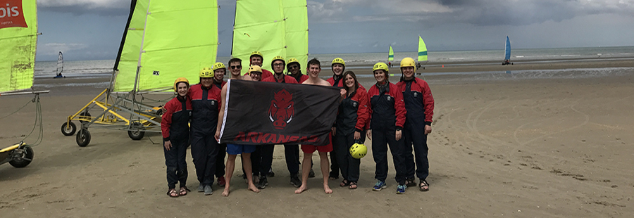 Students standing on beach with razorback flag in Belgium