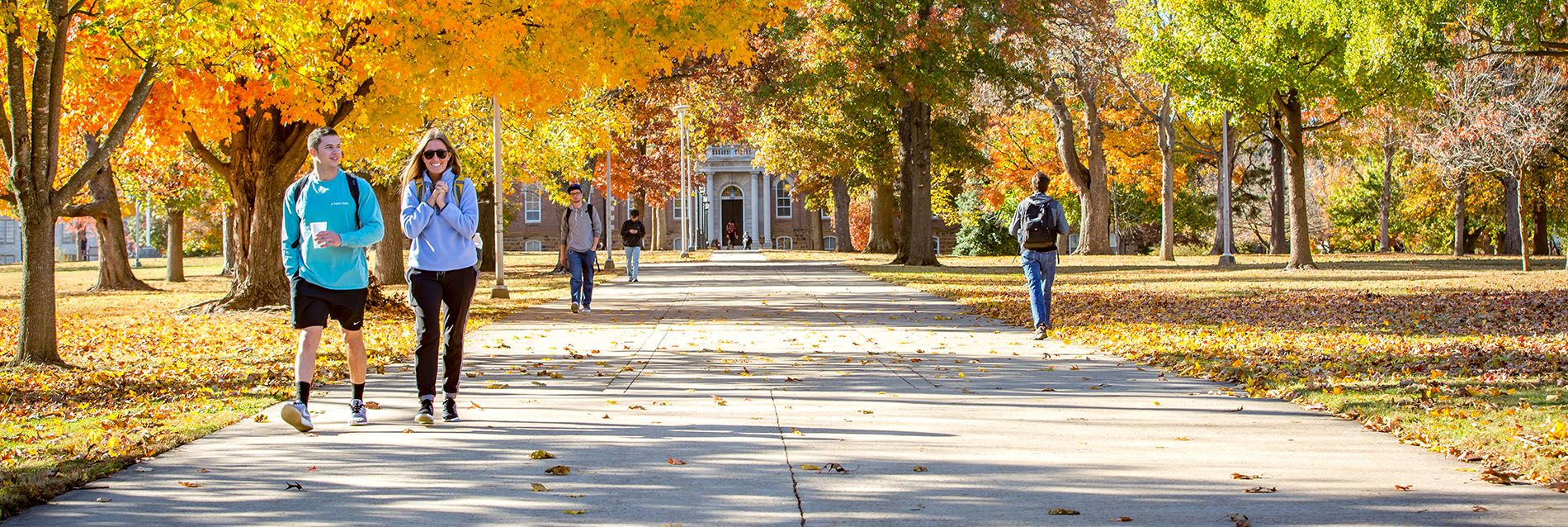 Student Walking Down The Sidewalk In Front Of Old Main