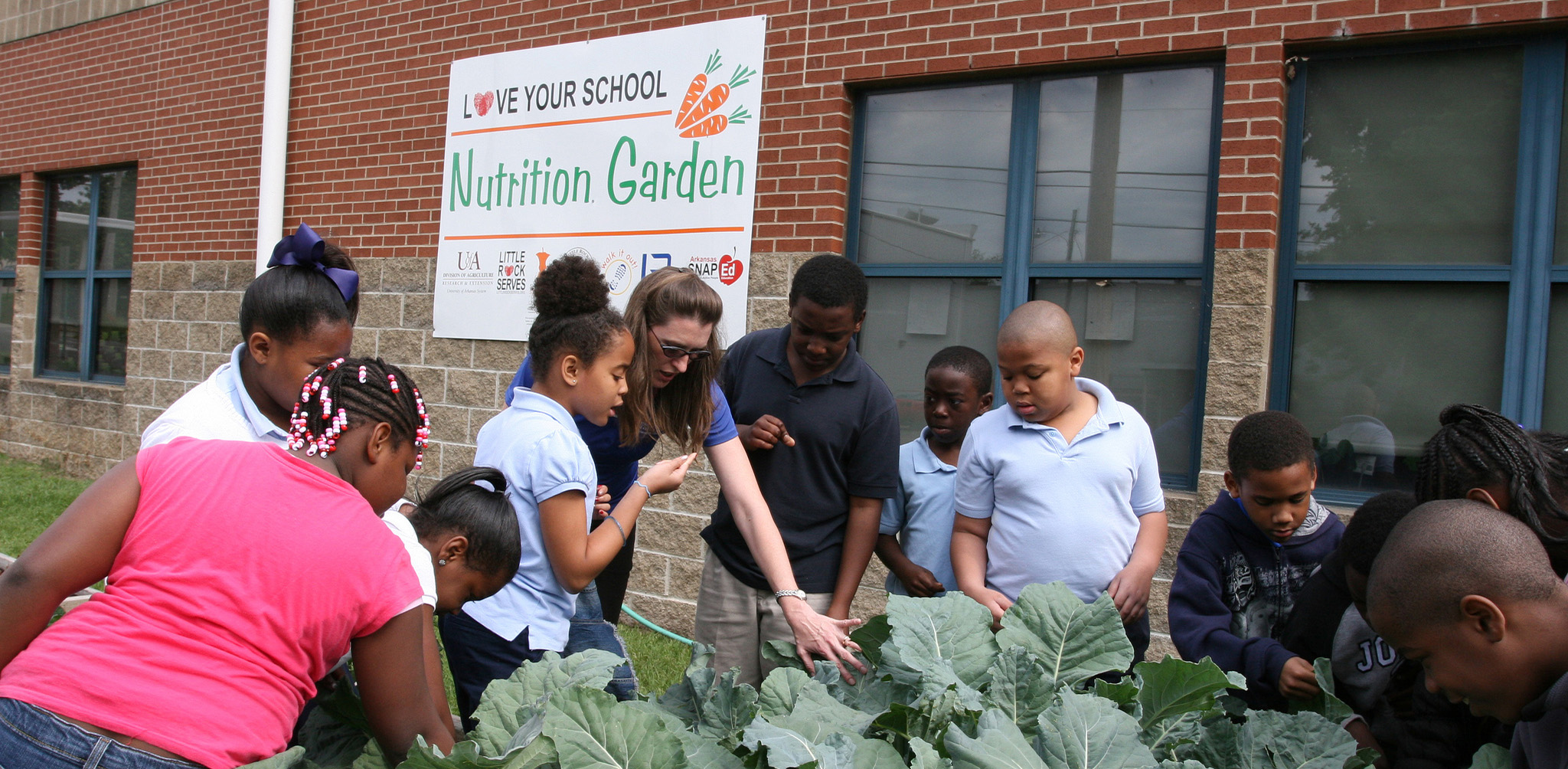 Instructor with young students outside working in a school garden. Photo by the Arkansas Cooperative Extension Service.