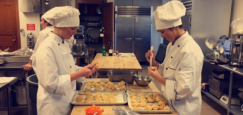 Students working in Maple Bistro plating food.